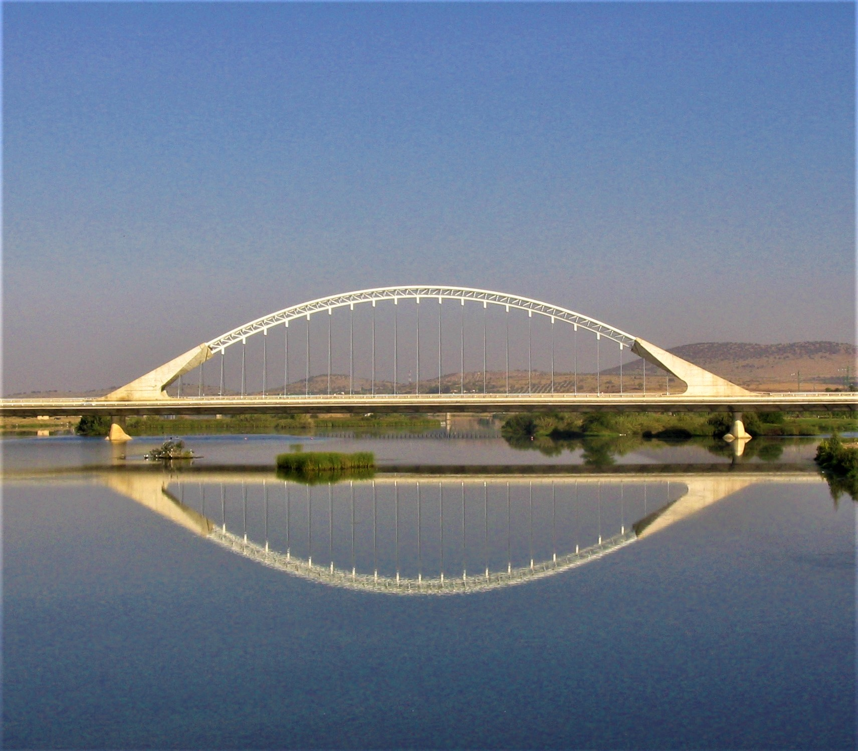 a reflection of the New Bridge over the River Guadiana taken from the Roman Bridge
